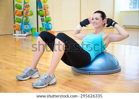 woman doing exercises for abdominal muscles on bosu ball in gym - stock photo