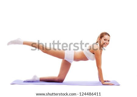 woman doing exercises on mat isolated over white - stock photo