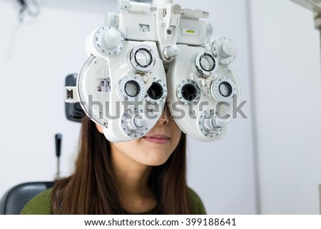 Woman doing eye test in medical office - stock photo