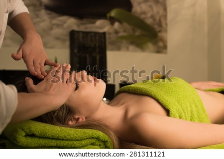 Woman doing face massage in spa clinic - stock photo