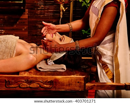 Woman doing facial massage in tropical spa in Indian. SPA salon decorated with bamboo. - stock photo
