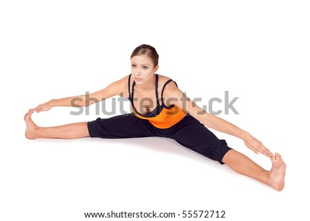 Woman doing first stage of yoga exercise called Seated Wide Angle Pose, sanskrit name: Upavista Konasana, this pose frees spine and hip joints, relieves sciatica, improves circulation in pelvic region - stock photo