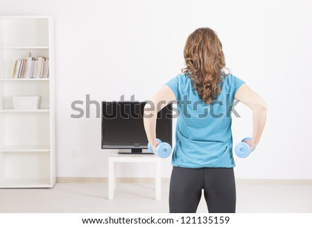 Woman doing fitness at home with dumb-bells using on screen TV instructions - stock photo