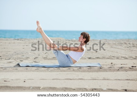 woman doing fitness exercise on beach on a sunny day