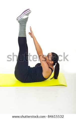 Woman doing fitness exercise on yellow mat - stock photo