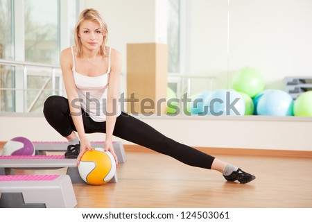 Woman doing fitness in a gym with a ball - stock photo