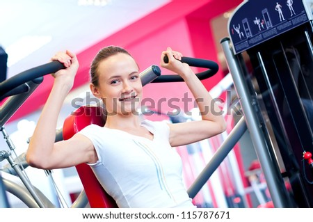 Woman doing fitness training on a butterfly machine with weights in a gym