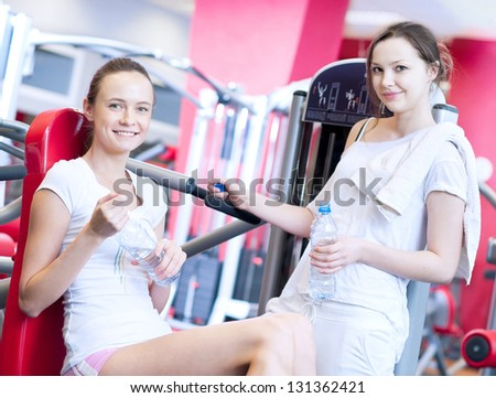 Woman doing fitness training on a butterfly machine with weights in a gym with friend - stock photo