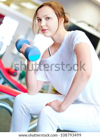 Woman doing fitness training  with dumbbell weights in a gym - stock photo