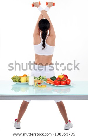 Woman doing gym workout in front of vegetables - stock photo