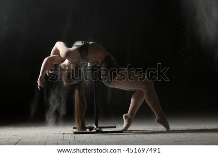 Woman doing gymnastic element on stand while sprinkled flour - stock photo
