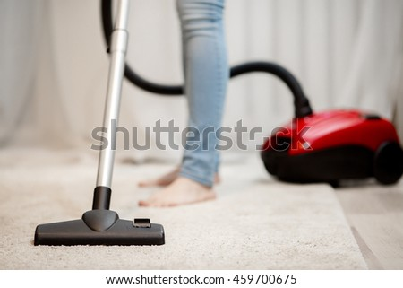 Woman doing house cleaning, vacuuming carpet with thick pile