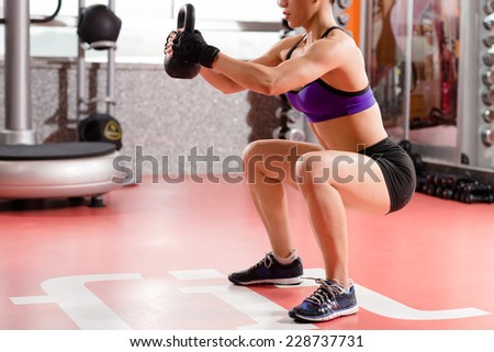 Woman doing kettlebell weight exercise indoors