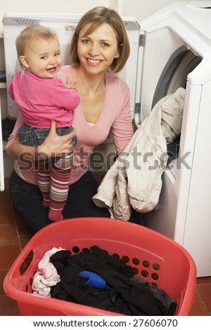 Woman Doing Laundry And Holding Baby Daughter - stock photo