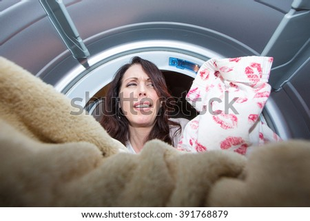 Woman doing laundry upset with kiss stained underwear - stock photo