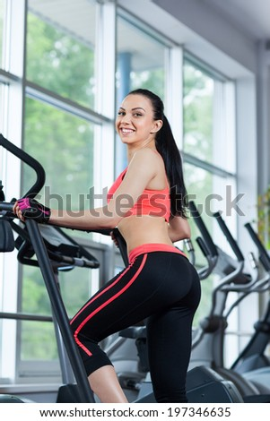 Woman doing legs exercise on stair steppers machine, young girl smile in gym fitness center - stock photo