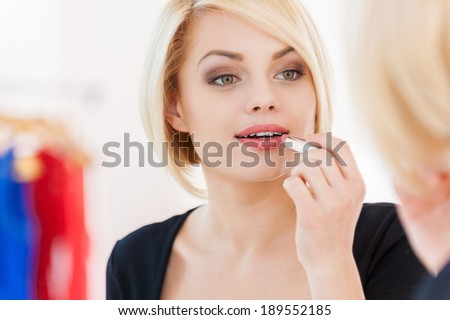 Woman doing make-up. Beautiful young blond hair woman doing make-up and smiling while looking at the mirror - stock photo