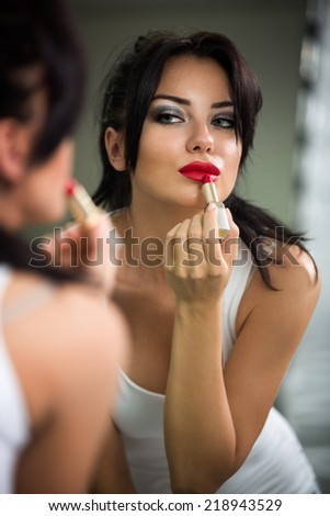 Woman doing make-up, beautiful young woman doing make-up and smiling while looking at the mirror - stock photo