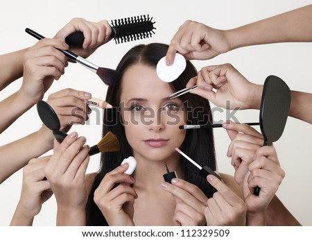 woman doing make up with many hands and arms helping her get the job done faster - stock photo