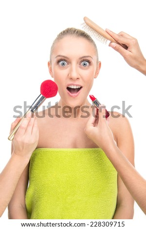 woman doing make up with many hands and arms helping her get the job done faster. girl making emotional surprised face on white background - stock photo