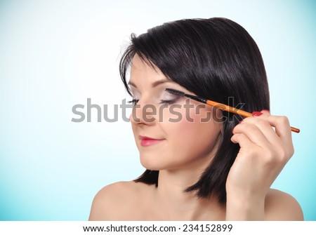 woman doing makeup eyelashes on a blue background - stock photo