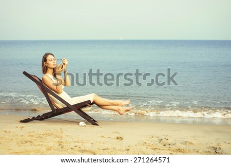 woman doing makeup outdoor on the beach
