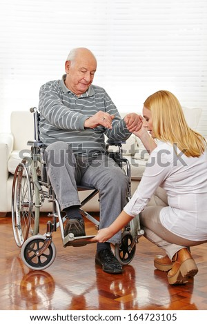 Woman doing physiotherapy with senior man in wheelchair - stock photo