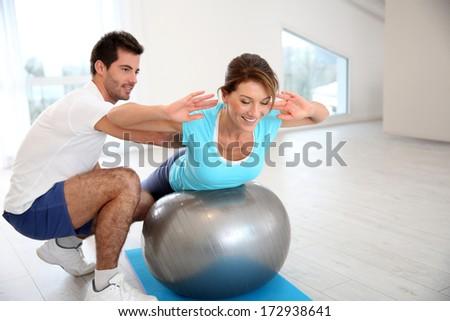 Woman doing pilates exercises with coach - stock photo