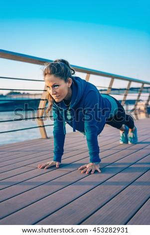 Woman doing plank on riverside - stock photo