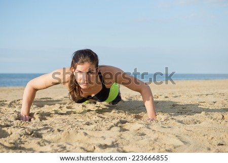 Woman doing push ups on a beach on a warm summer evening. - stock photo