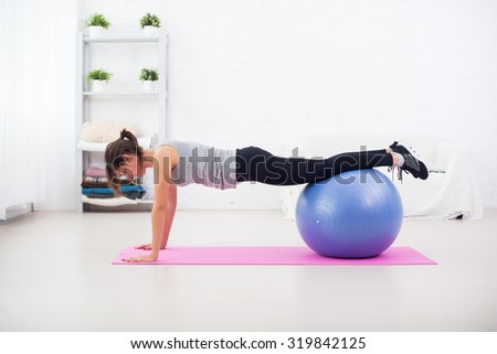 Woman doing push-ups on the floor with fit ball in her living room an exercise mat at home.