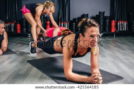 Woman doing push ups with trainer in background - stock photo