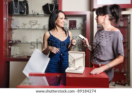woman doing shopping at the jewellery store and paying by credit card - stock photo