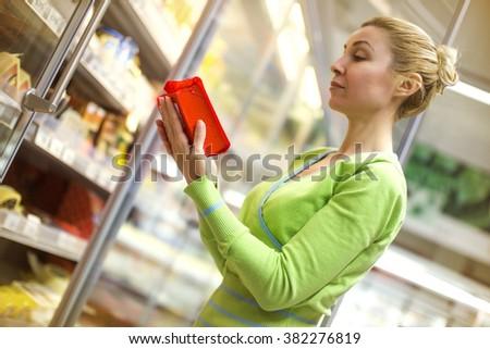 Woman doing shopping of merchandise in supermarket.Horizontal shot.  - stock photo