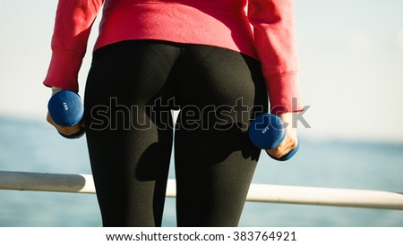 Woman doing sports outdoors with dumbbells. Fit fitness girl in sportswear on seaside exercising  - stock photo