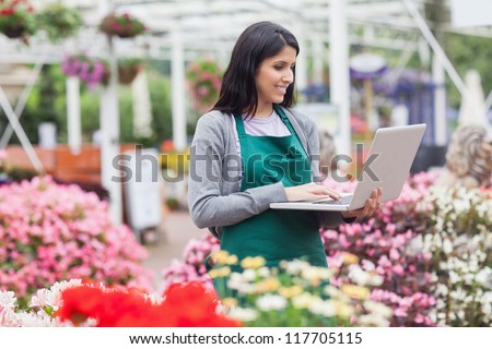 Woman doing stocktaking with laptop in garden centre - stock photo