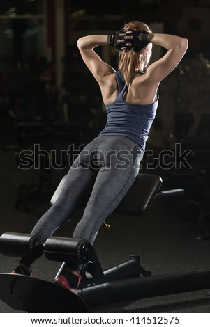 Woman doing strength exercises for abdominal muscles at indoor sport gym. Girl doing yoga stretches after running. Fitness model in dark sport club.  - stock photo