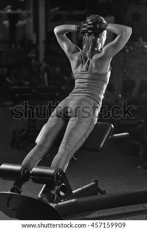 Woman doing strength exercises for abdominal muscles at indoor sport gym. Girl doing yoga stretches after running. Fitness model in dark sport club. Black and white. - stock photo