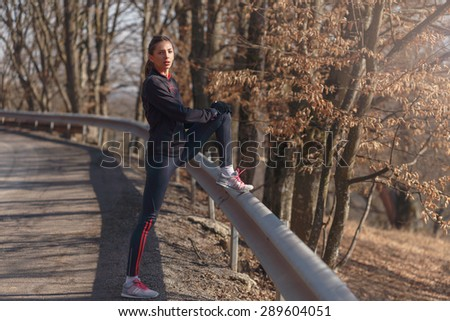 Woman doing stretching before jogging in sunny autumn day - stock photo