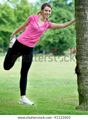 Woman doing stretching exercise for her legs outdoors - stock photo