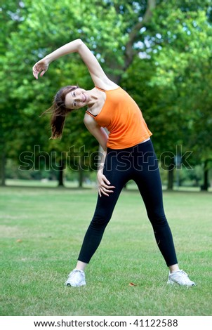 Woman doing stretching exercise in the park - stock photo