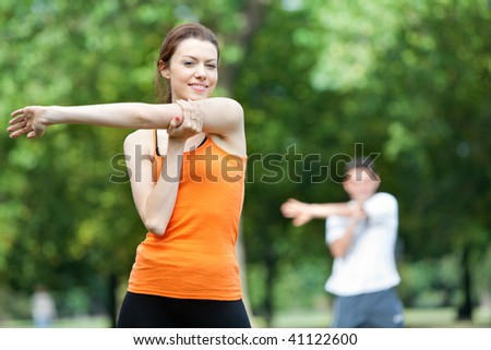 Woman doing stretching exercises in a class outdoors - stock photo