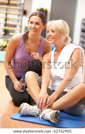 Woman Doing Stretching Exercises In Gym With Trainer - stock photo