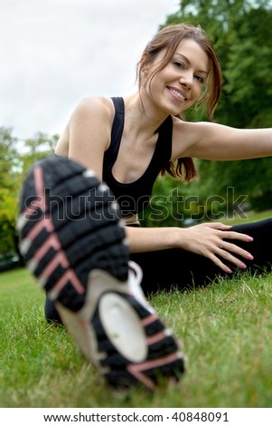 woman doing stretching exercises on the floor outdoors - stock photo