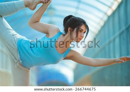Woman doing stretching yoga exercises outdoors on the bridge.  - stock photo