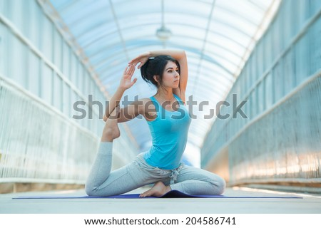 Woman doing stretching yoga exercises outdoors on the bridge. Full Length  - stock photo