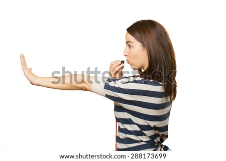 Woman doing the stop gesture and using a whistle - stock photo