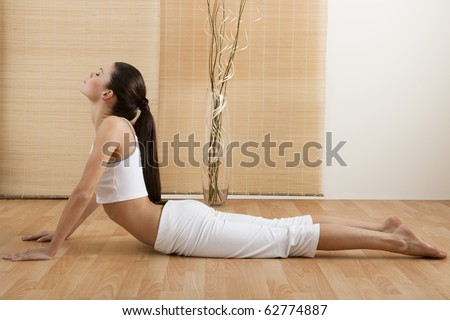 Woman doing Upward Dog Yoga Position, part of Sun Salutation - stock photo