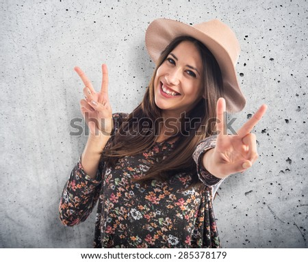 woman doing victory gesture over textured background - stock photo