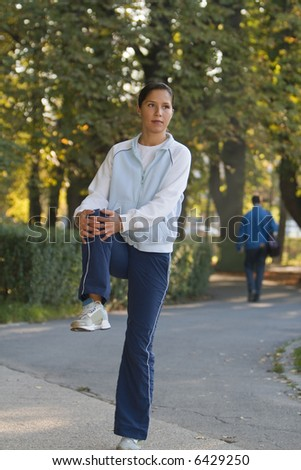 Woman doing waring-up movements in a park in autumn. - stock photo